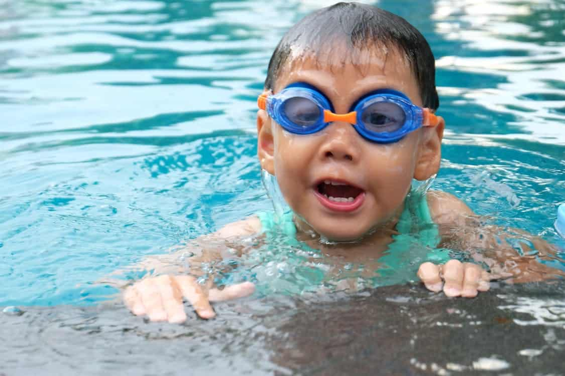 Young Child Swimming in Pool with Goggles
